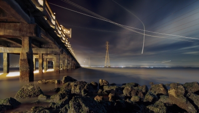 Planes headed for San Francisco International Airport descend past the former and current San Mateo Bridges under a moonlit sky